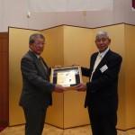 春の叙勲を受章した三須衛さん(昭和33年卒業)へ記念品を渡す三橋会長
